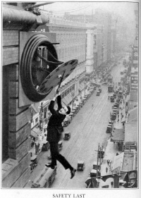 Harold Lloyd clutching the hands of a large clock as he dangles from the outside of a skyscraper above moving traffic